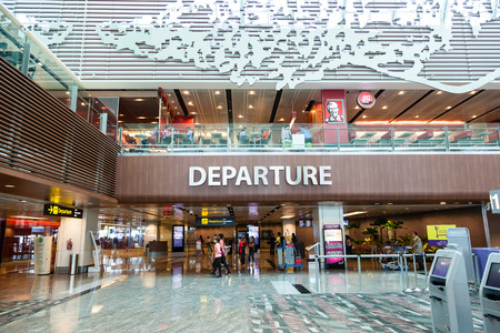 Travelers walk about Singapore Changi Airport's departure hall. With three passenger terminals it is one of the largest transportation hubs in Asia with a total annual handling capacity of 66 million passengers. Éditoriale