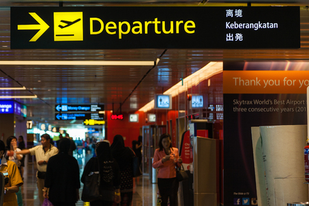 arrival departure board: A departure sign hangs over busy travellers at Changi Airport Terminal 1 departure hall. Opened in 1981 Changi Airport is a major transportation hub in Asia and serves more than 100 airlines traveling to some 200 cities worldwide. Editorial
