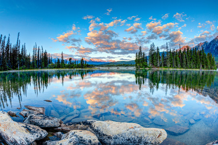 Canada: First glimpse of golden sunrise at Pyramid Lake in Jasper National Park, Alberta, Canada. The clouds reflect off the calm waters. Stock Photo