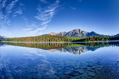 Colorful trees lined the shores of Patricia Lake at Jasper National Park with Pyramid Mountain in the background. The calm lake reflects a mirror image of the mountains and trees. 스톡 콘텐츠