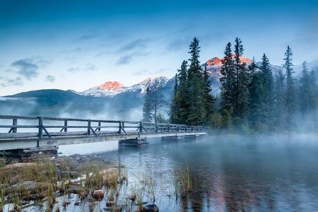 ピラミッド湖ジャスパー国立公園、アルバータ、カナダで霧と霧の朝の黄金日の出の最初の一見。木製の橋は、湖のピラミッド島に します。