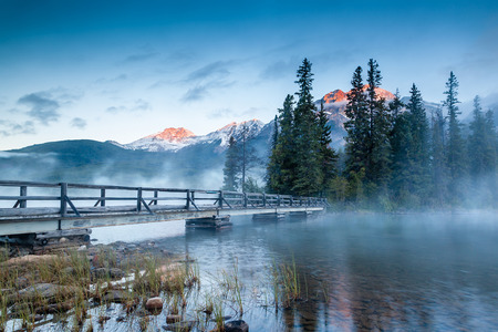 First glimpse of a golden sunrise on a misty and foggy morning at Pyramid Lake in Jasper National Park, Alberta, Canada. The wooden bridge leads to Pyramid Island on the lake. Imagens