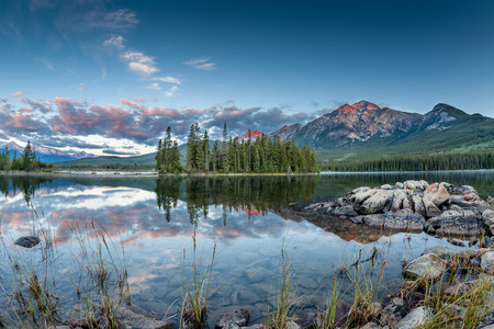 glimpse: First glimpse of golden sunrise at Pyramid Lake in Jasper National Park, Alberta, Canada. The clouds and Pyramid Mountain reflect off the calm waters. Stock Photo