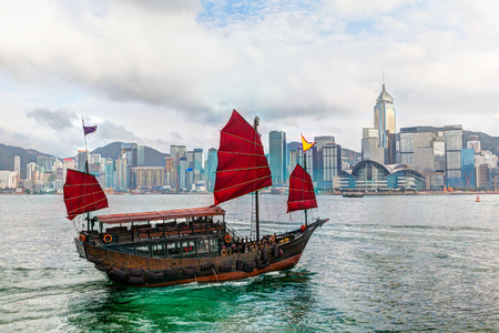 victoria harbor: HDR rendering of a typical Chinese junk ship with red sails on Victoria Harbor in Tsim Sha Tsui, Hong Kong. The emerald-colored sea water and low clouds near sunset created a colorful glow on the skyline in the background.