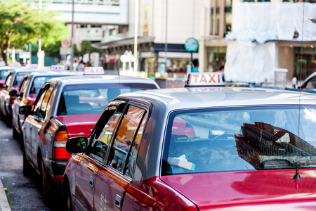 taxi sign: A fleet of Hong Kong taxis waiting at a taxi stand. Hong Kong taxis are easily recognizable by their red and white colors. Editorial