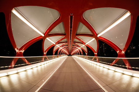 peace: Night view of Calgarys Peace Bridge. The bridge features a red and white helix design and was opened in March 2012. It connects the extensive Bow River Pathway on the north and south sides of the Bow River. Stock Photo