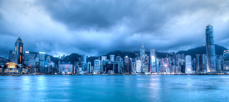 HONG KONG: Wide-angle view of Hong Kong skyline on Victoria Harbor taken at the blue hour after sunset. Viewed from downtown Tsim Sha Tsui on Hong Kong Island. HDR rendering.
