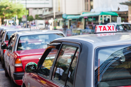 taxi sign: A fleet of Hong Kong taxis waiting at a taxi stand. Hong Kong taxis are easily recognizable by their red and white colors. Focus on foreground Taxi sign with shallow depth of field on long line.