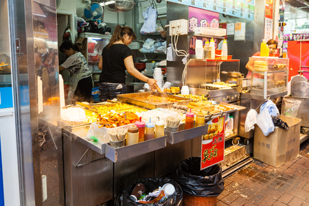 A street vendor selling popular snacks at Fa Yuen Street market in Kowloon. These include stinky tofu, pig intestines, fishballs, beefballs and seafood served on skewers and dipped in a variety of sauces. Editorial
