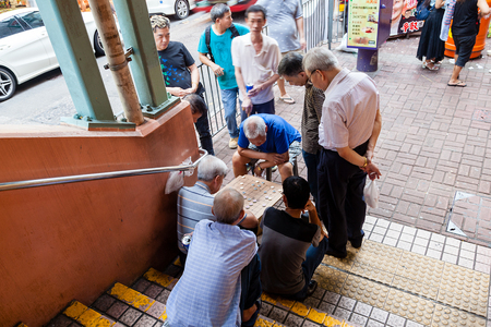 playing the market: A group of elderly men engage in a game of Chinese Chess on the street corner of Fa Yuen Street in Kowloon.  Playing Chinese chess in public parks, surrounded by watching crowds, is a common sight and pastime in Hong Kong.