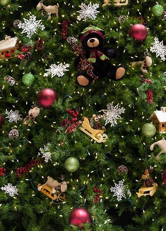닫기 싸구려, 눈송이, 테디 베어, 썰매, 진저 하우스, 소나무 콘 및 조명 장식 크리스마스 트리를 닫습니다. 스톡 콘텐츠