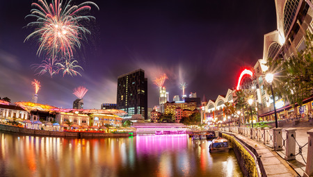 singapore cityscape: Fireworks set off in the backdrop to the Singapore River along Clarke Quay as a precursor to Singapores 50 years of independence celebration. The area used to be a commercial center during the colonial era where warehouses are located. Now, it is convert