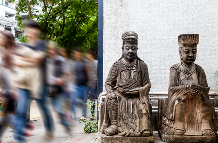 deities: Hurried passersby on a street corner in Hong Kong where 2 generic statues of Chinese deities stood guard. Despite modernation and the fast-paced life, the majority of Hong Kongers follow and practice various forms of Chinese religious beliefs.