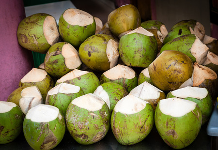 isotonic: Bunch of coconuts with the top cut ready for sale at a street market. Coconut drinks are super hydrating. They are low in calories, naturally fat- and cholesterol free and contain more potassium than four bananas. Stock Photo