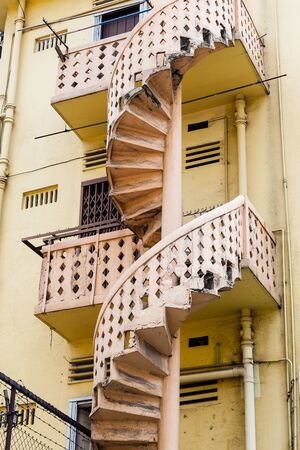 back alley: Back alley Victorian-style spiral staircase of an old colonial building in Singapore. Stock Photo