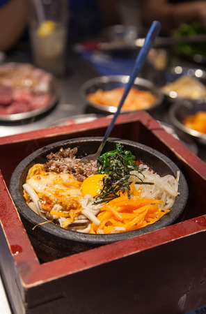 vertical orientation: Hot Stone Korean Bi Bim Bap, a traditional signature dish with kimchi vegetables, gochujang chili pepper paste, doenjang fermented soybean paste topped with raw egg and sliced beef. Vertical orientation.