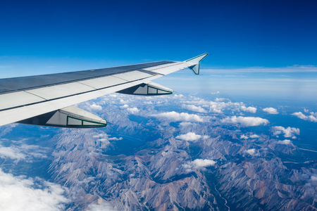 Airplane window view showing wing of plane flying over clouds and Rocky Mountains.