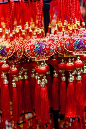 signify: Chinese New Year ornaments on sale. These common ornaments have the Chinese word meaning Blessings printed on them. They are typically hung at home to signify good luck.