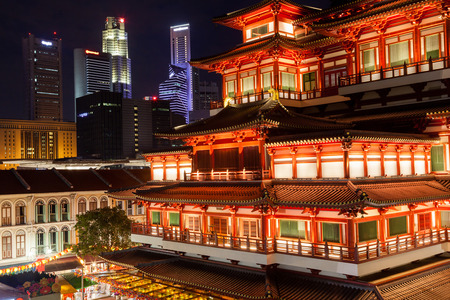 chinatown: Night view of the Buddha Tooth Relic Temple in Singapore Chinatown, with city skyline in the background.