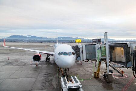 バンクーバー国際空港出発ゲートの旅客ターミナルにサービスを提供されて駐機場に民間航空機。