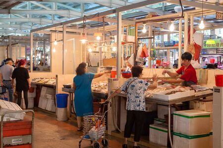 fishmonger: A fishmonger at a local wet market in Singapore helping a customer. For local residents, a wet market is the place to buy groceries and the freshest produce.