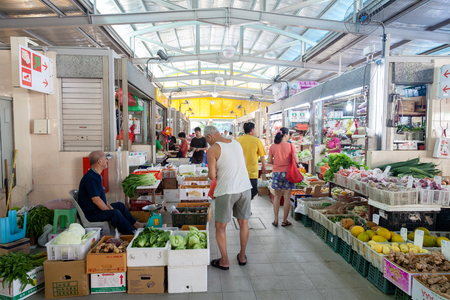 Local residents shopping for fruits and vegetables at a local wet market in Singapore. For residents, a wet market is the place to buy groceries and the freshest produce. Éditoriale