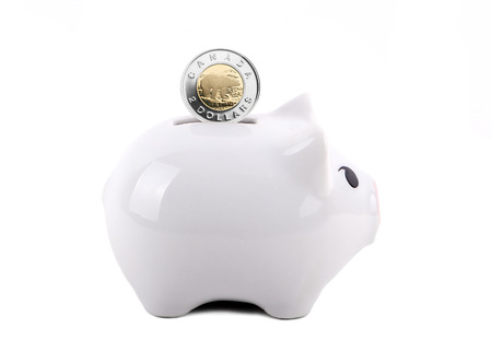 White piggy bank with Canadian dollar coin in the slot. Concept of saving for a rainy day, education, retirement, etc. Isolated on White. Stock Photo