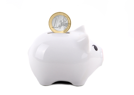 coin bank: White piggy bank with Euro dollar coin in the slot. Concept of saving for a rainy day, education, retirement, etc. Isolated on White. Stock Photo