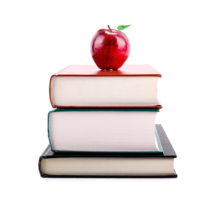 A red apple on a stack of books isolated on white background. Concept of education, back to school, learning, teaching, literacy.