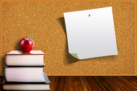corkboard: Education concept with apple on stack of books on corkboard background. Pinned paper on board with copy space.