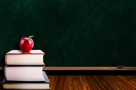 Education-Konzept mit Apfel auf Stapel Bücher auf Tafel Hintergrund. Kopieren Sie Platz auf Kreidetafel. Standard-Bild