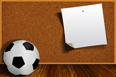 paper board: Soccer ball and with cork board background and copy space on pinned piece of paper. Stock Photo