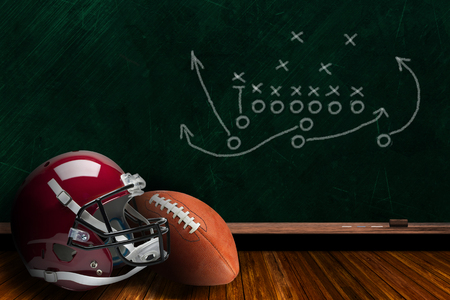Football helmet and ball with play strategy drawn on a background chalk board with copy space.