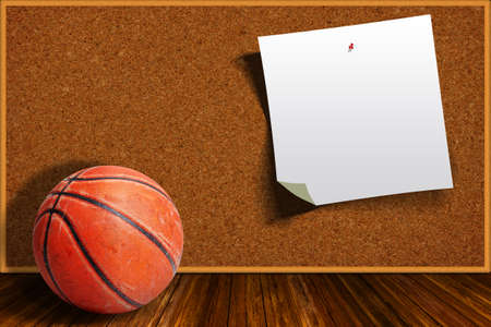 Basketball on a background cork board with copy space on pinned paper.
