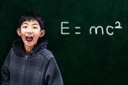 asian boy: Smart Asian boy with in classroom setting with Math equation on chalkboard background and copy space