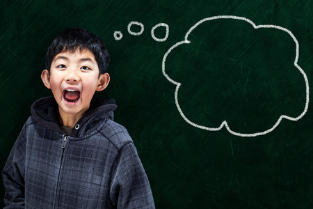 wide open spaces: Smart Asian boy mouth wide opened in classroom setting with chalkboard background and thought bubble copy space. Stock Photo