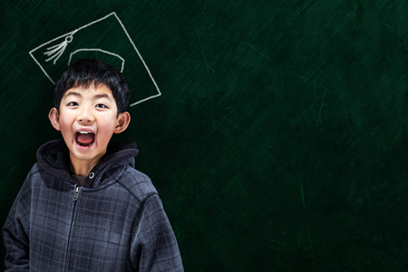wide open spaces: Jubilant Asian boy in classroom setting with graduate hat on chalkboard background and copy space. Concept for university education and future aspirations.