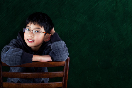 asian boy: Smart Asian boy sitting on classroom chair with chalkboard background and copy space.