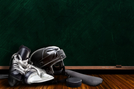 Ice hockey equipment consisting of skates, helmet, stick and puck with background chalk board copy space.