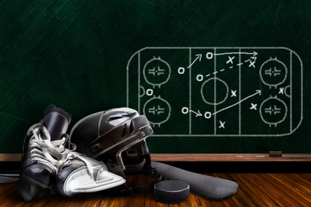 Ice hockey equipment consisting of skates, helmet, stick and puck with background play strategy drawn on chalk board with copy space.