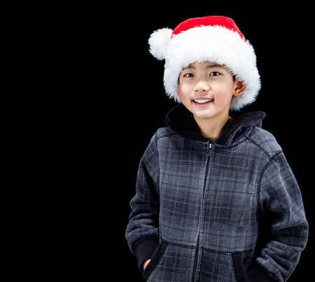 fleece: Cute Asian boy in Christmas mood wearing Santa Hat and fleece hoodie, isolated on black background. Copy Space.