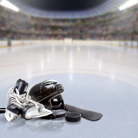Hockey arena full of fans in the stands with helmet, skates, stick and puck on ice and copy space. Deliberate focus on equipment and shallow depth of field on background.