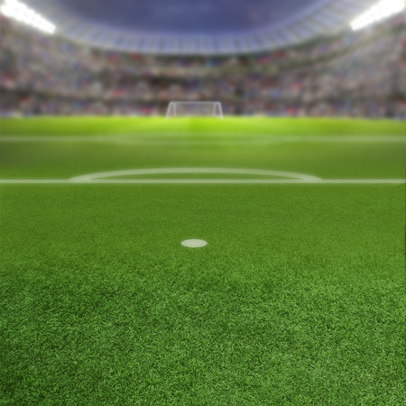 copy space: Soccer stadium full of fans in the stands with deliberate focus on foreground penalty box and shallow depth of field on background. Floodlights flare for effect and copy space. Stock Photo