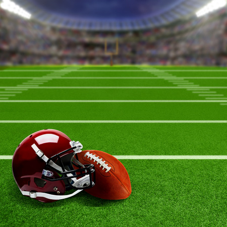 campo calcio: stadio di calcio americano pieno di tifosi in tribuna con casco da football e palla sul campo. focalizzazione intenzionale su apparecchiature e primo piano con profondit� di campo su sfondo. Proiettori allo stallo per l'effetto e lo spazio della copia.
