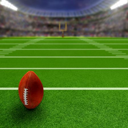 terrain de foot: stade de football américain plein de fans dans les tribunes avec le football en position verticale prêt sur le terrain. accent Deliberate sur l'équipement et de premier plan avec une faible profondeur de champ sur fond. Projecteurs flare pour un effet et une copie de l'espace.