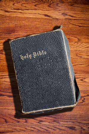 deliberate: An old Bible against a wood textured background and copy space. Deliberate side lighting with hard shadow for dramatic effect.