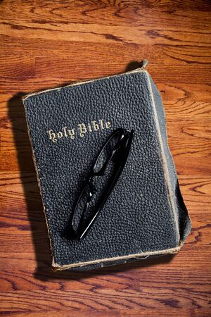 deliberate: An old Bible with a pair of glasses on it against a wood textured background and copy space. Deliberate side lighting with hard shadow for dramatic effect.