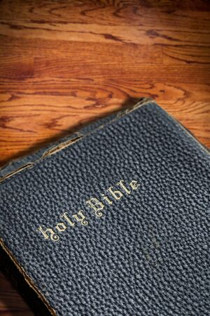 deliberate: Closeup focus on the title of an old holy Bible with deliberate shallow depth on vignette wood texture background. Angled lighting for dramatic shadow effect and copy space.