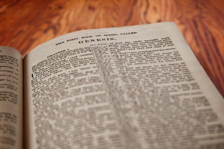 Close-up van een oude Heilige Bijbel opengesteld voor het beroemde boek Genesis op een rustieke houten tafel. Opzettelijke focus op de titel met ondiepe scherptediepte op de achtergrond. Deze vertaling is King James, dat is publiek domein.
