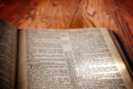 king james: Closeup of an old Holy Bible opened to the famous verse of John 3:16 and highlighted by a beam of light. Book on a rustic wooden table with deliberate focus on the verse with shallow depth of field on background. This translation is King James, which is p Stock Photo